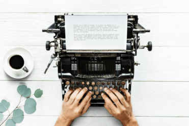 This image shows two hands using a typewriter to write a nonprofit fundraising appeal
