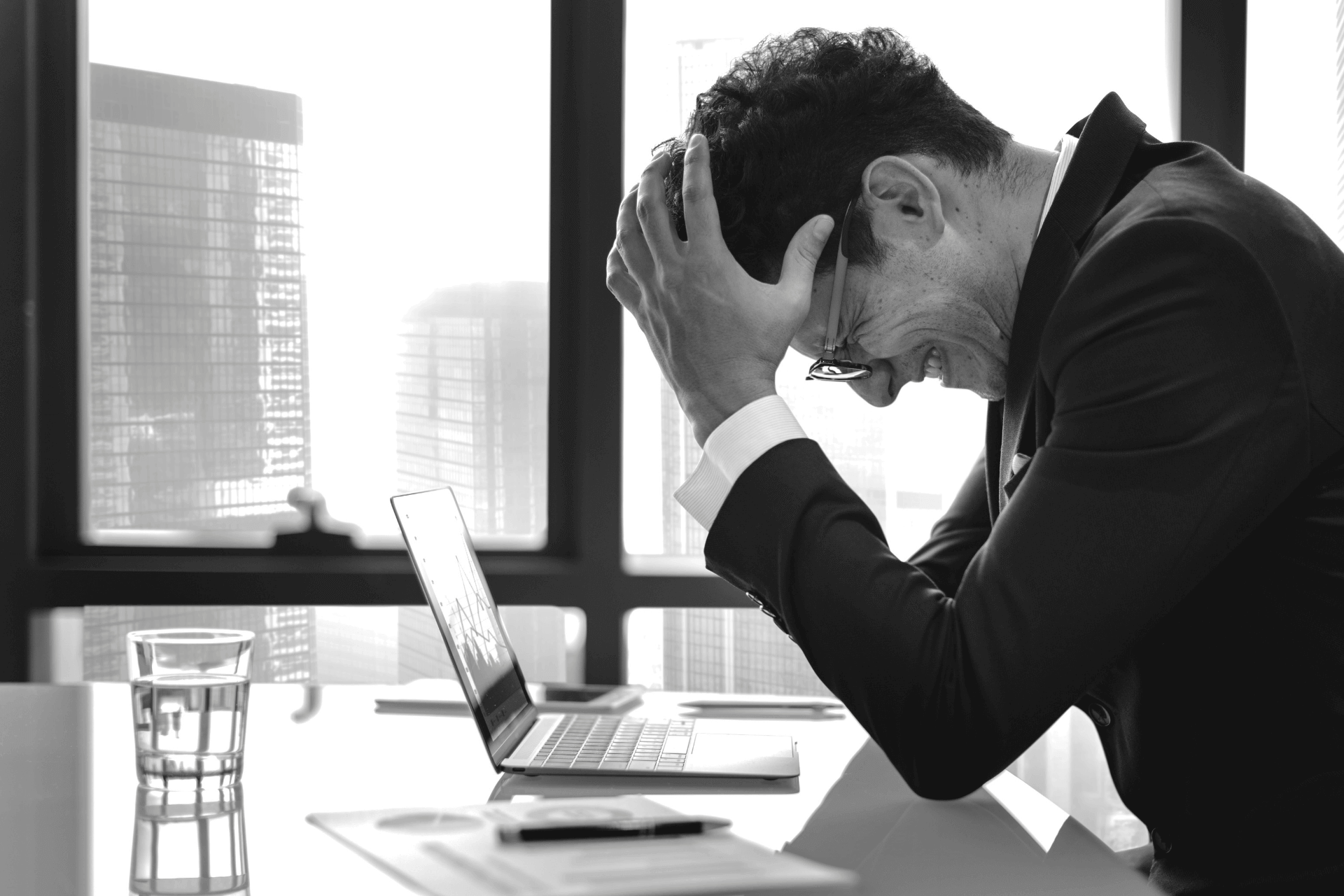 This image shows a man sitting at his desk with his hands on his head feeling fear about fundraising