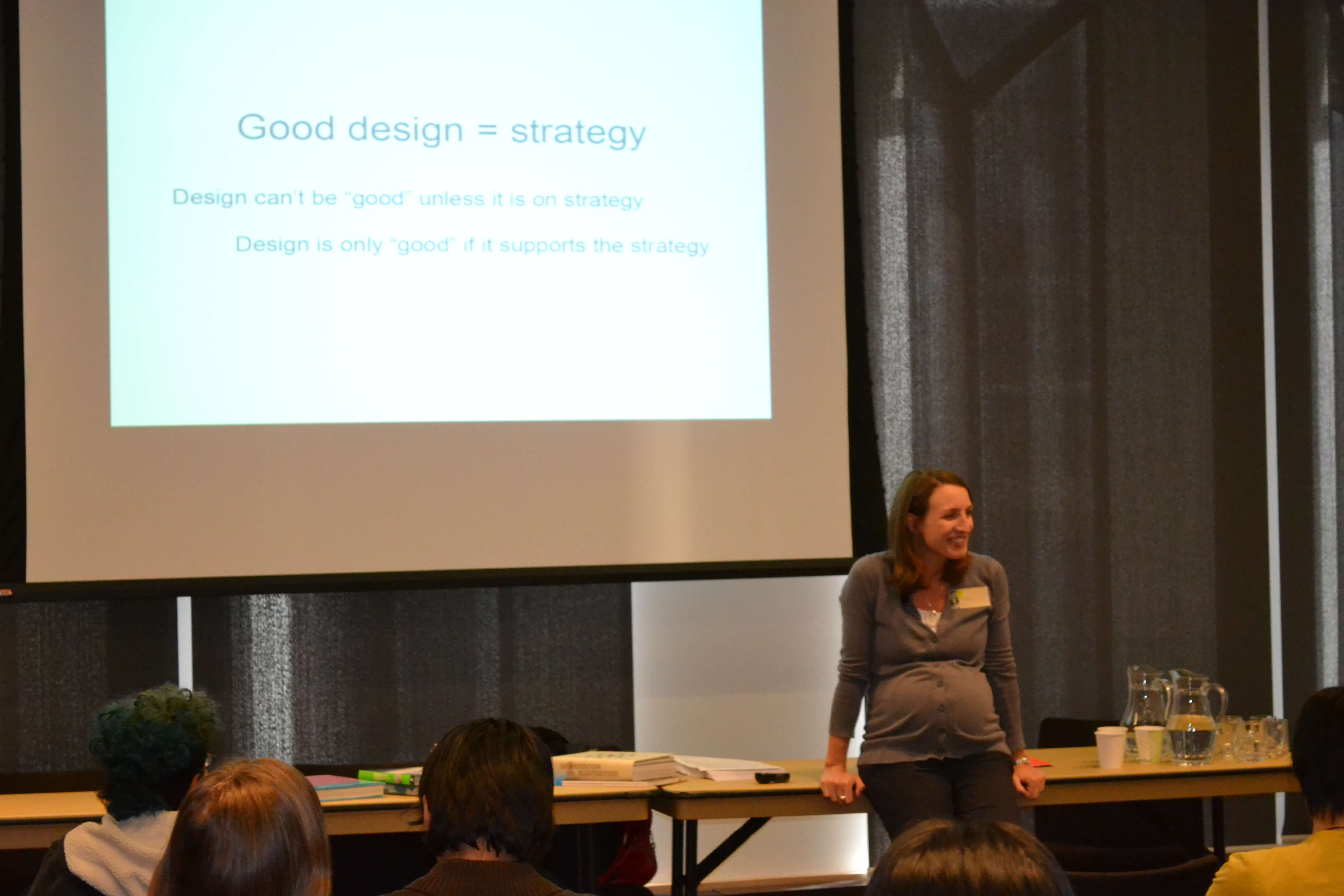 An image of Laura Sellors standing in front of a Good design = strategy slide