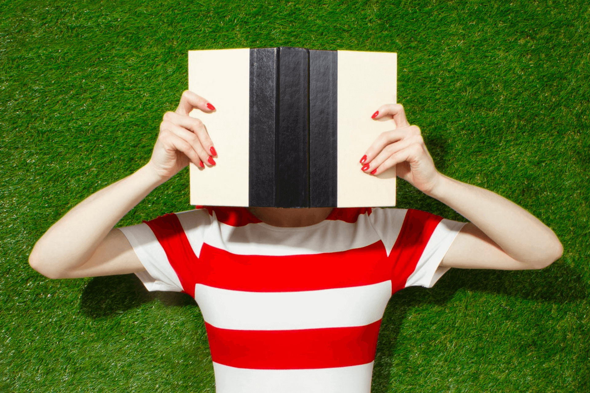 Woman covering her face with an opened book