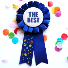 "Image of a ribbon with confetti around it. The ribbon says ""The Best""."