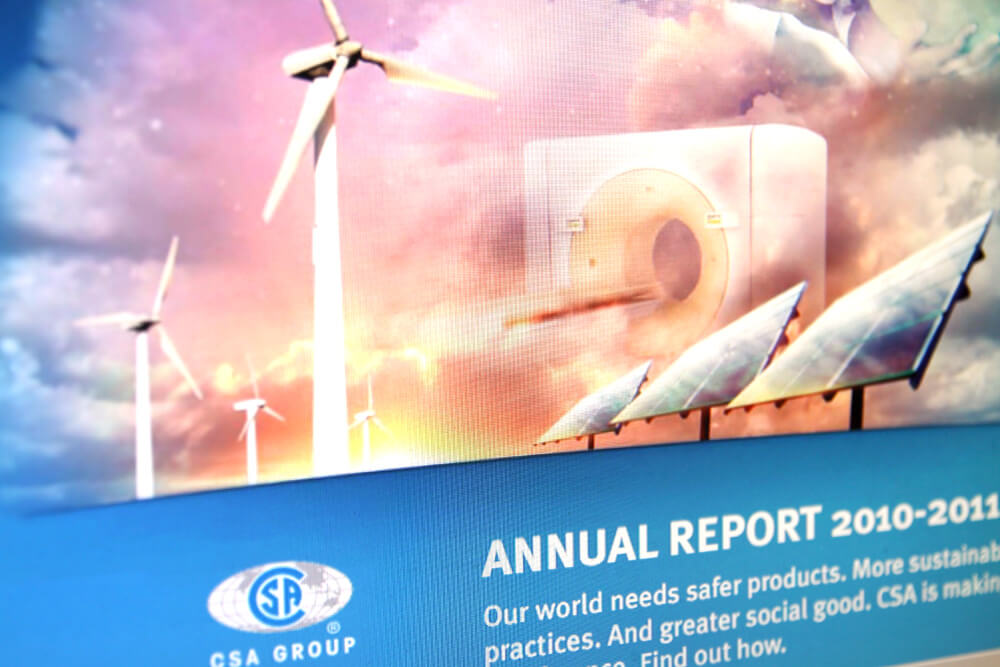 Image of the cover of the CSA 2010/11 annual report which has 3 windmills and 3 solar panels with clouds in the background.