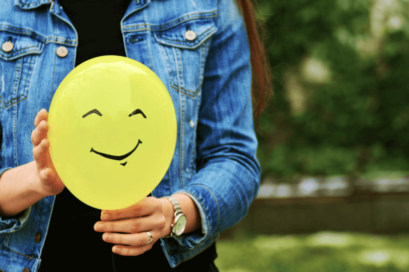 This image shows a person holding a smiley representing the importance of good donor retention strategies for nonprofits