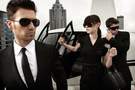 An image of two men and a women in formal clothing exiting a helicopter