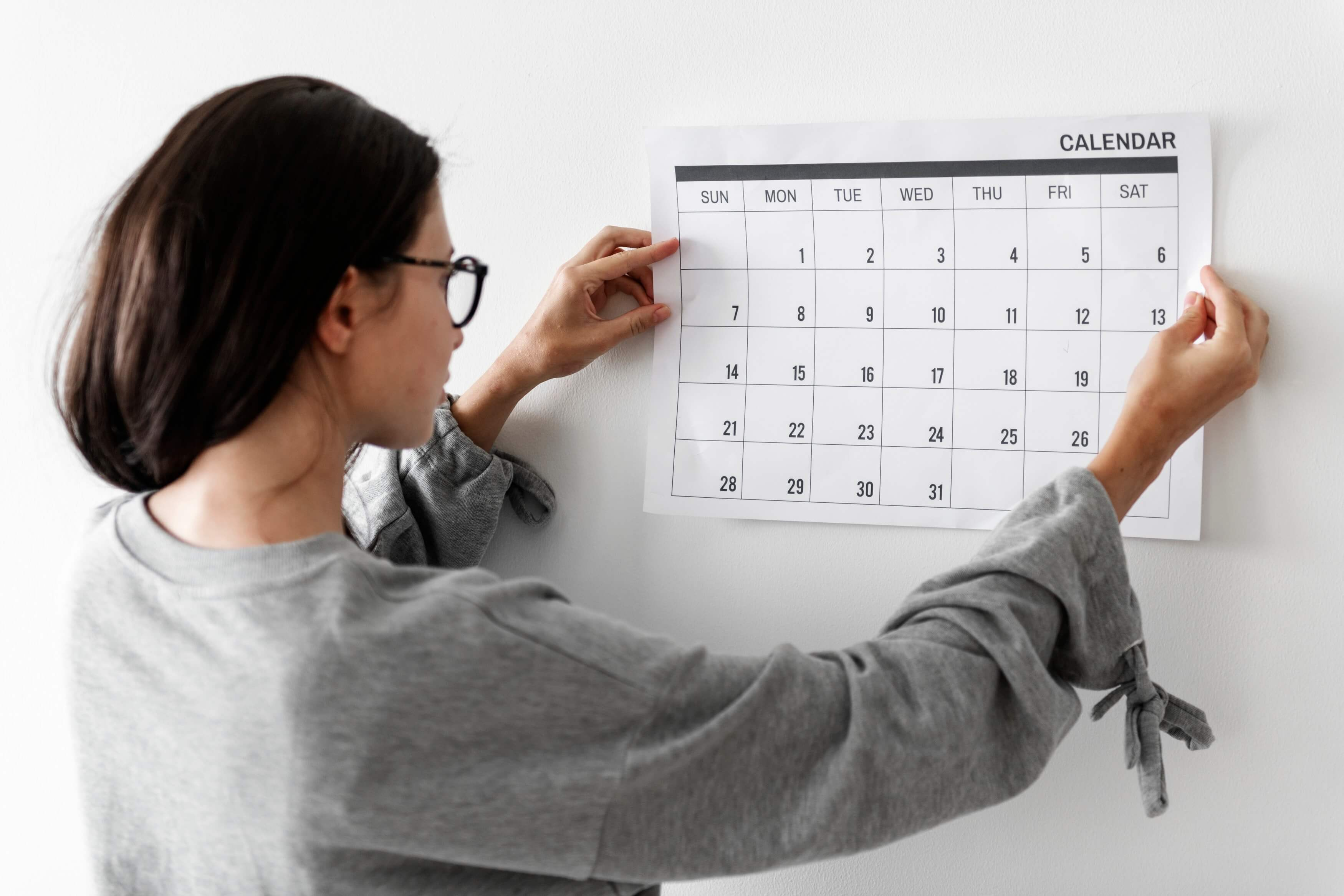 Woman putting calendar on the wall representing year-end fundraising for nonprofits