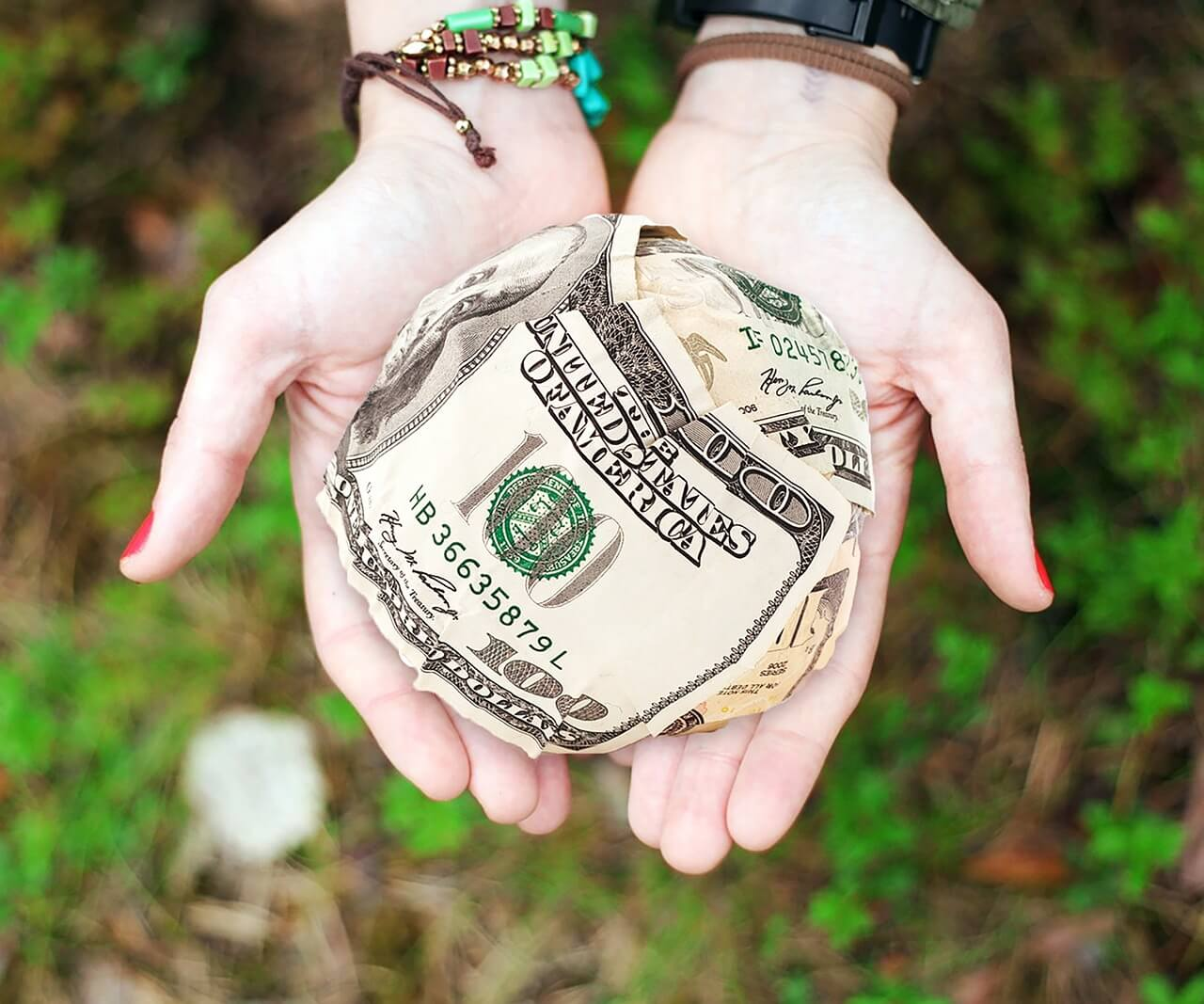 This image displays two hands holding money and portrays relevance to strategic marketing and data for nonprofit fundraising