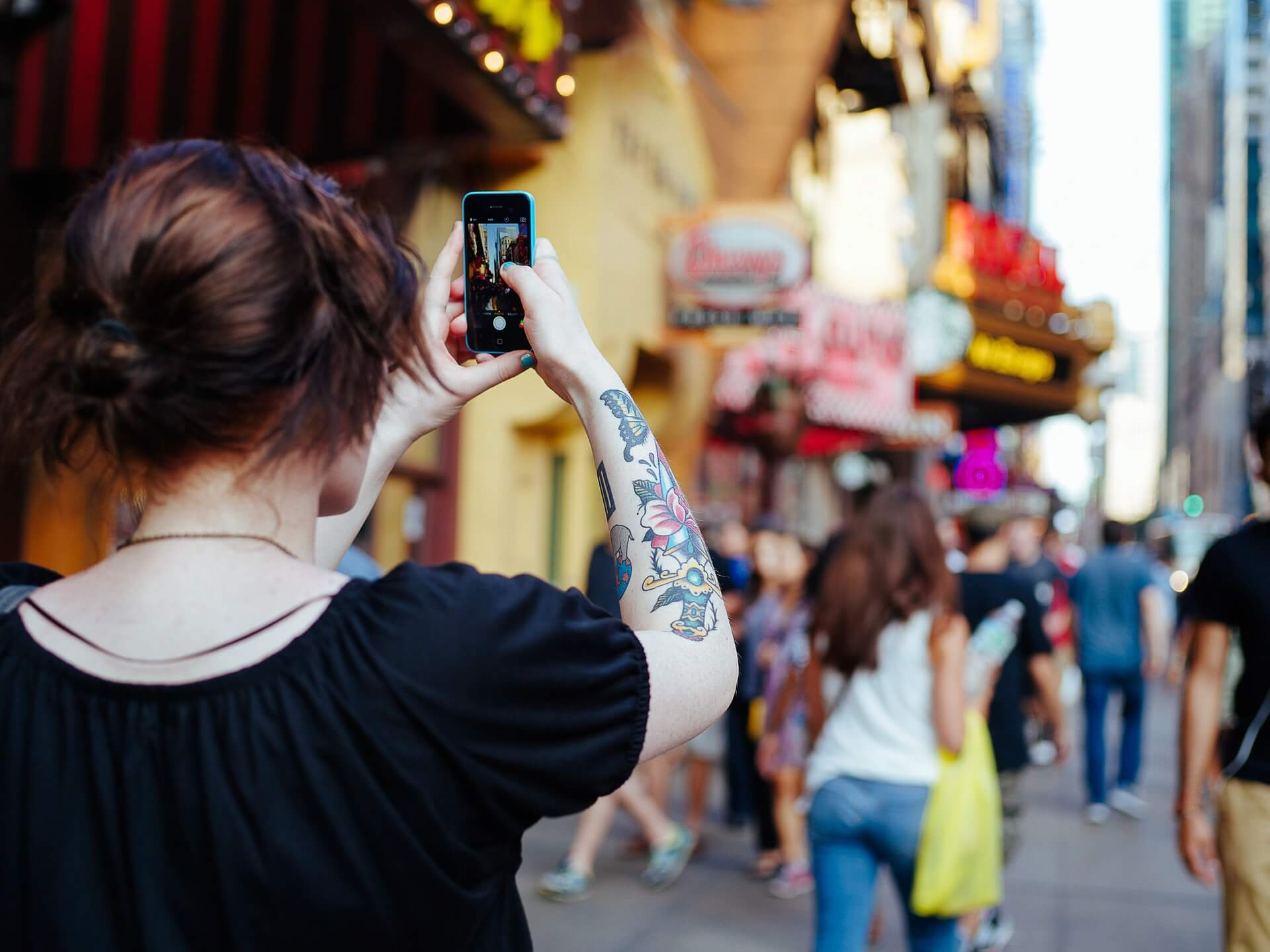 This image displays a millennial woman taking a picture with her phone and portrays relevance to social media and technology for nonprofit donations