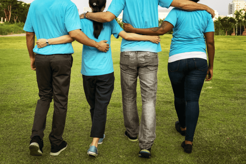 This image depicts the backs of four members of a small nonprofit with their arms around. Representing the unity of small nonprofits