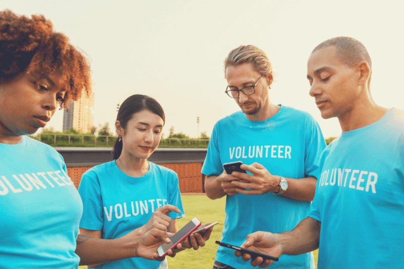 This image portrays four volunteers using social media features to show the good the nonprofit they support is doing